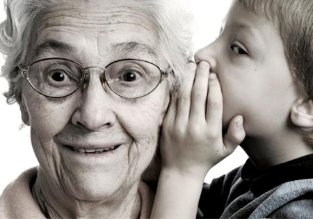 Photo of child whispering to Grandma